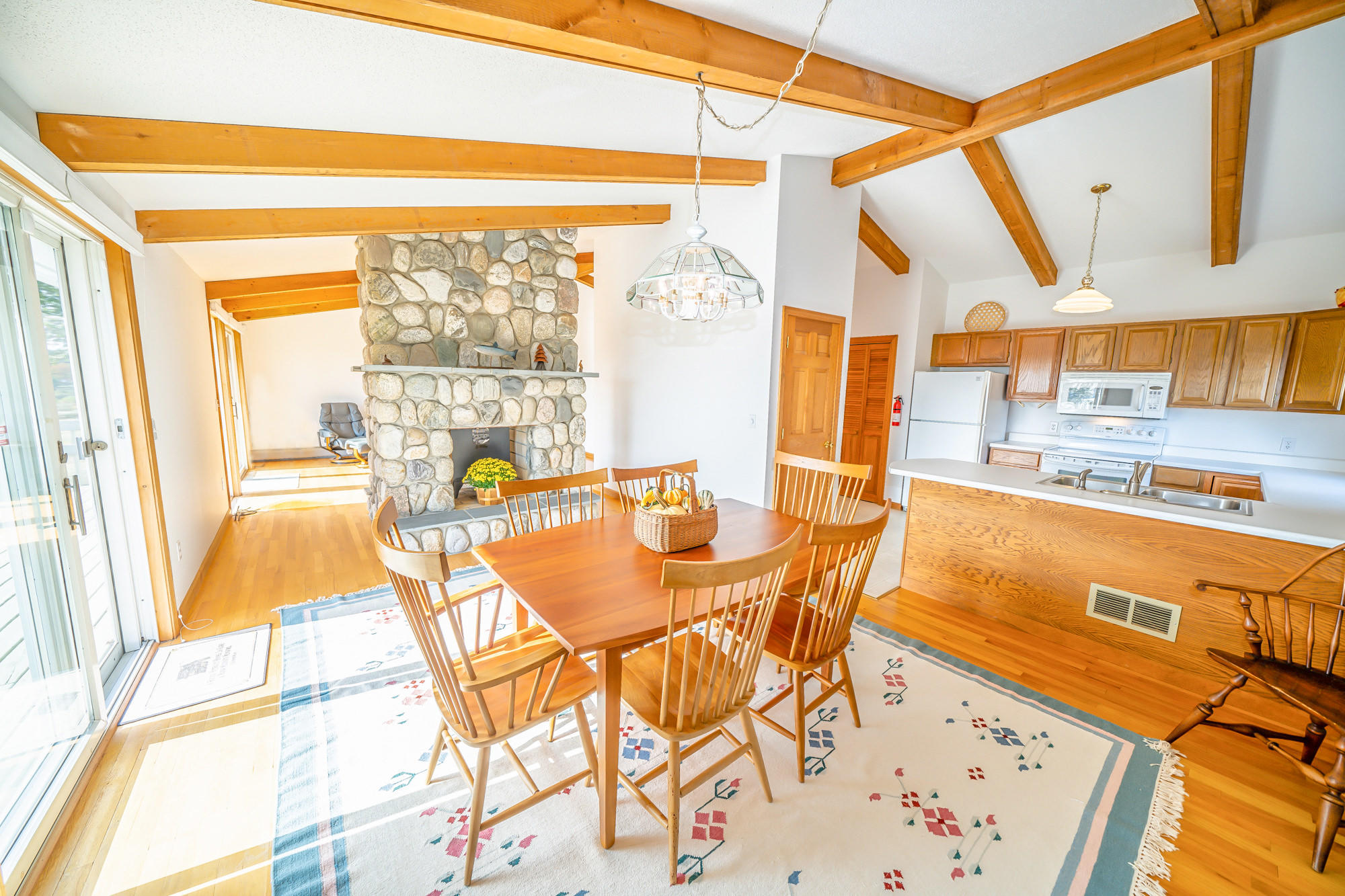 3-bedroom contemporary ranch offers a stone fireplace w/a wood-burning insert, exposed beams, hardwood floors, a spacious, water-view deck, a massive basement  with a work bench, 2 garages, a security system and an on-demand whole house generator.